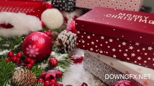 Footage - Red Christmas holiday gift box with falling snow and colorful decorated pine tree in background